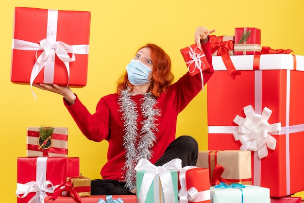 Vue de face de la jeune femme assise autour des cadeaux de noël en masque sur un mur jaune