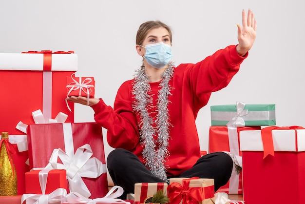 Vue de face jeune femme assise autour de cadeaux de noël en masque stérile