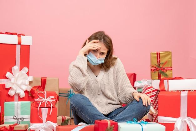 Vue de face jeune femme assise autour de cadeaux de noël en masque