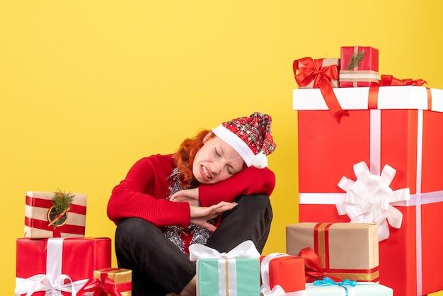 Vue de face de la jeune femme assise autour des cadeaux de noël sur mur jaune