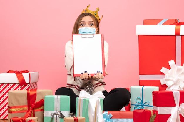 Vue de face jeune femme assise autour de cadeaux de noël avec note de fichier