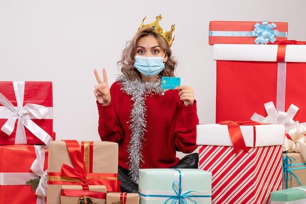 Vue de face jeune femme assise autour de cadeaux de noël tenant une carte bancaire