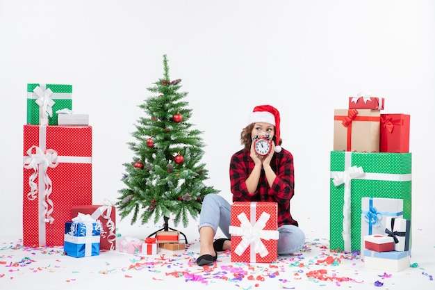Vue de face de la jeune femme assise autour de cadeaux de noël tenant des horloges sur un mur blanc