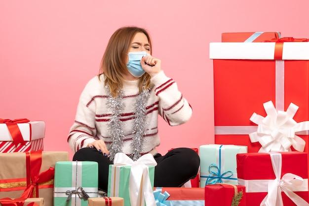Vue de face jeune femme assise autour de cadeaux de noël