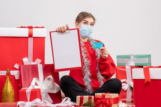 Vue de face jeune femme assise autour de cadeaux avec note et carte bancaire
