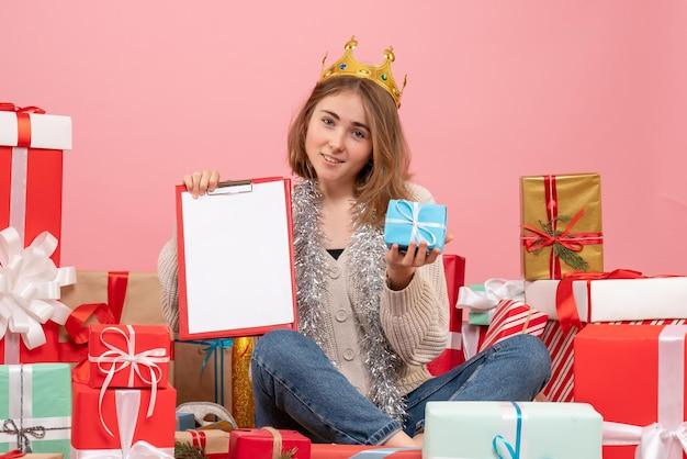 Vue de face jeune femme assise autour de cadeaux avec note dans ses mains