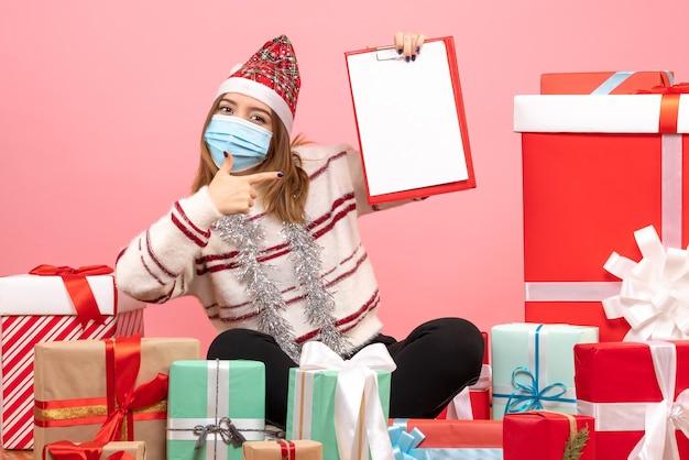 Vue de face jeune femme assise autour de cadeaux avec note de fichier