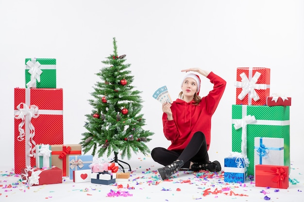 Vue de face de la jeune femme assise autour de cadeaux tenant des billets d'avion sur un mur blanc