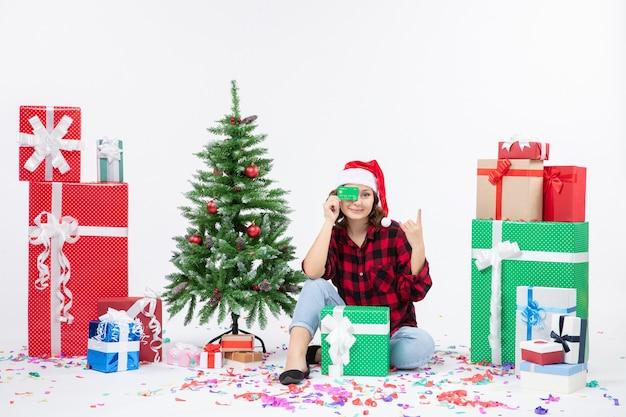 Vue de face de la jeune femme assise autour de cadeaux tenant une carte bancaire verte sur un mur blanc
