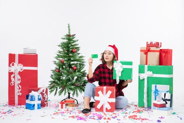 Vue de face de la jeune femme assise autour de cadeaux tenant une carte bancaire verte et présente sur mur blanc