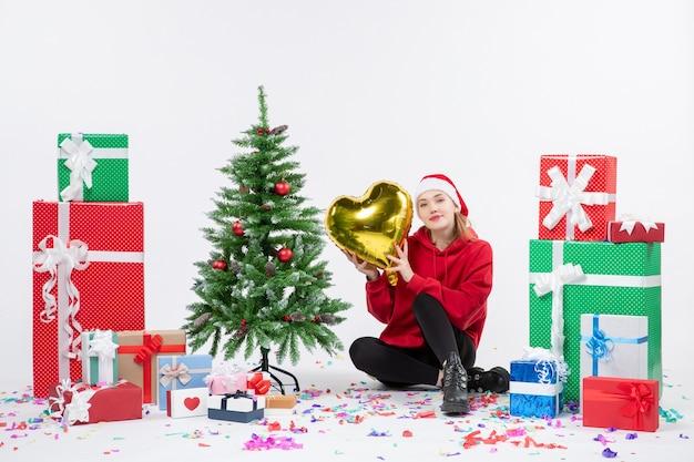 Vue de face de la jeune femme assise autour de cadeaux tenant la figure de coeur d'or sur le mur blanc