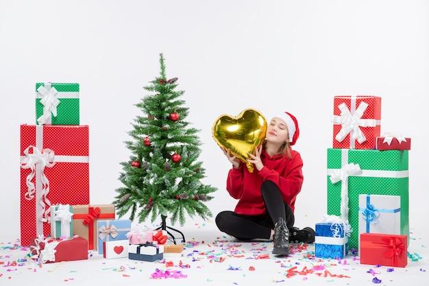 Vue de face de la jeune femme assise autour de cadeaux tenant la figure en forme de coeur or sur mur blanc