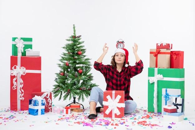 Vue de face de la jeune femme assise autour de cadeaux tenant des horloges sur sa tête sur un mur blanc