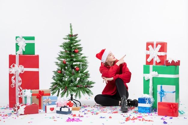 Vue de face de la jeune femme assise autour des cadeaux de vacances sur le mur blanc