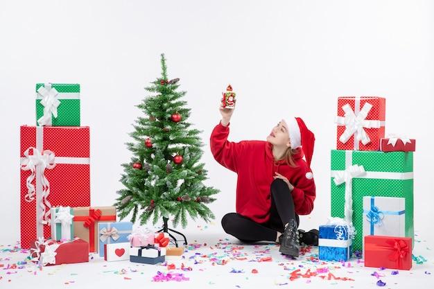Vue de face de la jeune femme assise autour des cadeaux de vacances tenant quelque chose sur le mur blanc