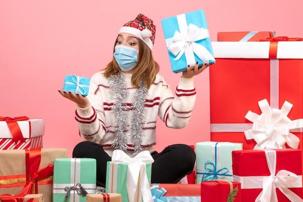 Vue de face jeune femme assise autour de cadeaux