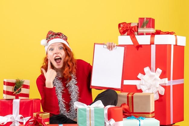 Vue de face de la jeune femme assise autour de différents cadeaux de noël sur mur jaune
