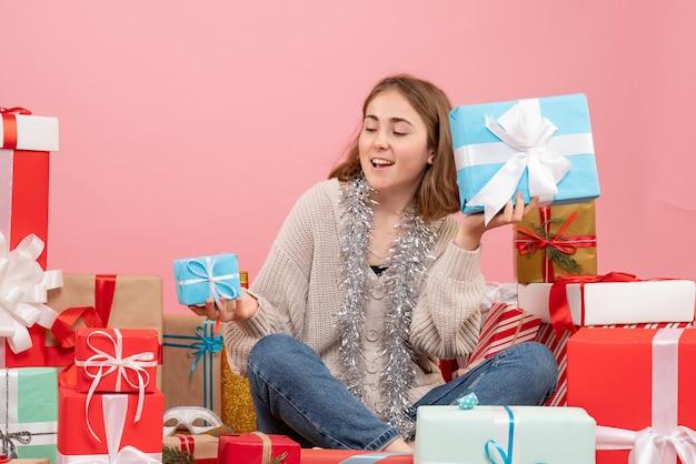 Vue De Face Jeune Femme Assise Autour De Différents Cadeaux Photo gratuit