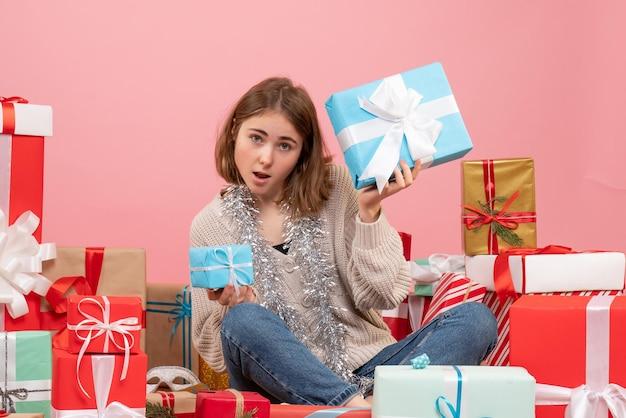 Vue de face jeune femme assise autour de différents cadeaux
