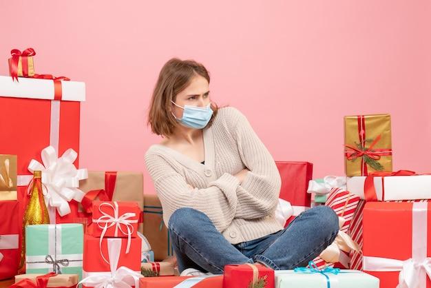 Vue De Face Jeune Femme Assise Autour De Noël Présente Dans Un Masque Stérile Photo gratuit