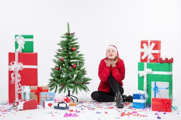 Vue de face de la jeune femme assise autour de vacances présente l'envoi de bisous sur le mur blanc