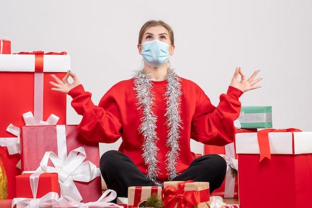 Vue de face jeune femme assise avec des cadeaux de noël en masque méditant