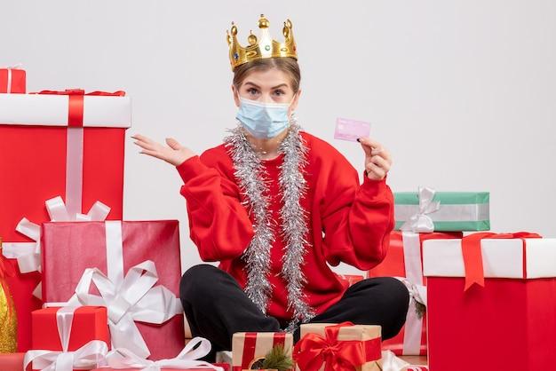 Vue de face jeune femme assise avec des cadeaux de noël en masque