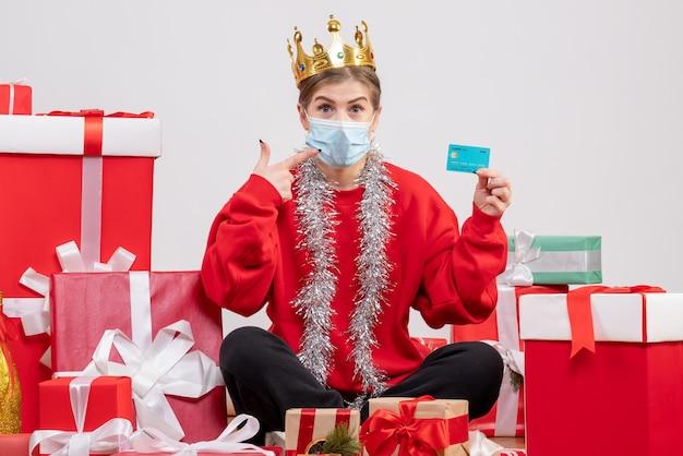 Vue de face jeune femme assise avec des cadeaux de noël tenant une carte bancaire