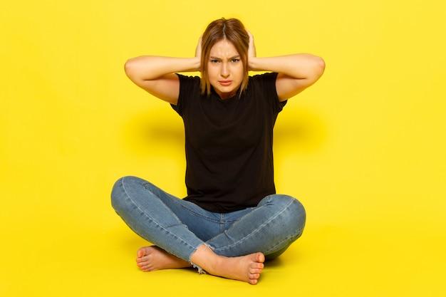 Une vue de face jeune femme assise en chemise noire et un jean bleu couvrant ses oreilles sur jaune
