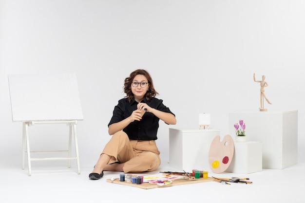 Vue de face jeune femme assise à l'intérieur de la pièce avec des peintures et un chevalet sur fond blanc