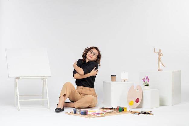 Vue de face jeune femme assise à l'intérieur de la pièce avec des peintures de chevalet et des glands sur fond blanc