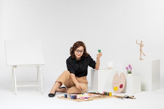 Vue de face jeune femme assise avec des peintures et chevalet sur fond blanc