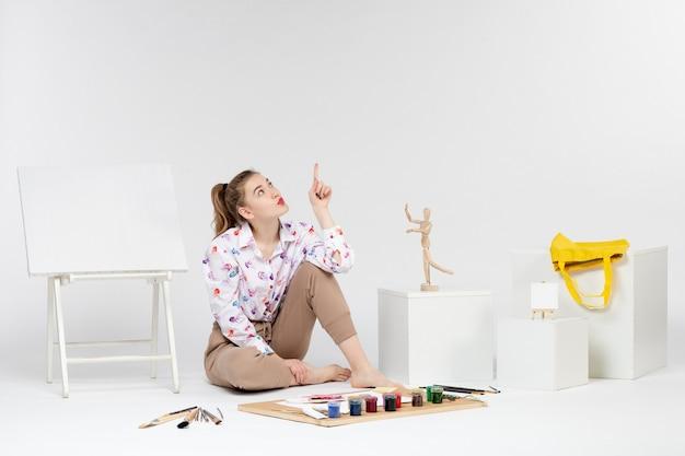 Vue de face jeune femme assise avec des peintures chevalet et pinceaux sur fond blanc