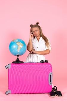 Vue de face d'une jeune femme assise avec un sac rose et un globe posant sur un mur rose