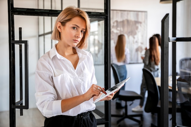 Vue de face jeune femme au bureau travaillant sur une tablette