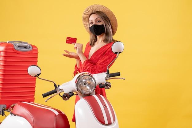 Vue de face jeune femme au chapeau panama tenant une carte de crédit près d'un cyclomoteur