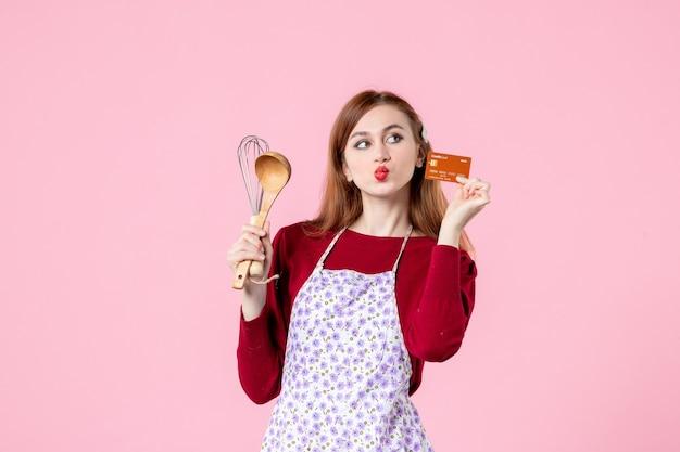 Vue de face jeune femme au foyer tenant un fouet et une carte bancaire sur fond rose tarte couleur cuisine cuisine cuisine femme gâteau nourriture argent