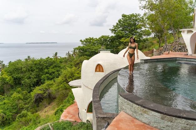 Vue de face d'une jeune femme aux cheveux noirs mince marchant dans une piscine à débordement