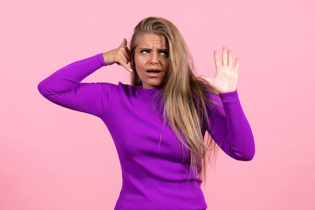 Vue de face d'une jeune femme en belle robe violette posant sur un mur rose clair