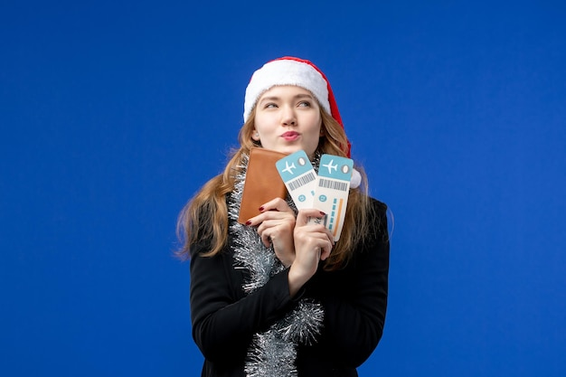 Vue de face d'une jeune femme avec des billets d'avion sur un mur bleu