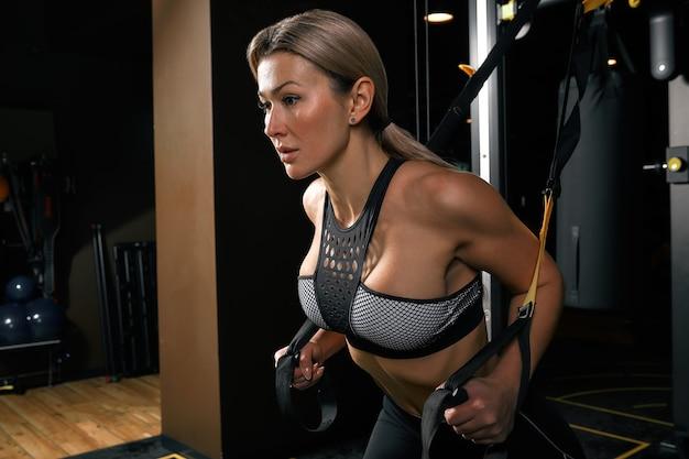 Vue de face de la jeune femme blonde confiante faisant des exercices de musculation séduisante jeune femme soulevant des haltères avec impatience forte forme du corps formé bras poitrine jambes