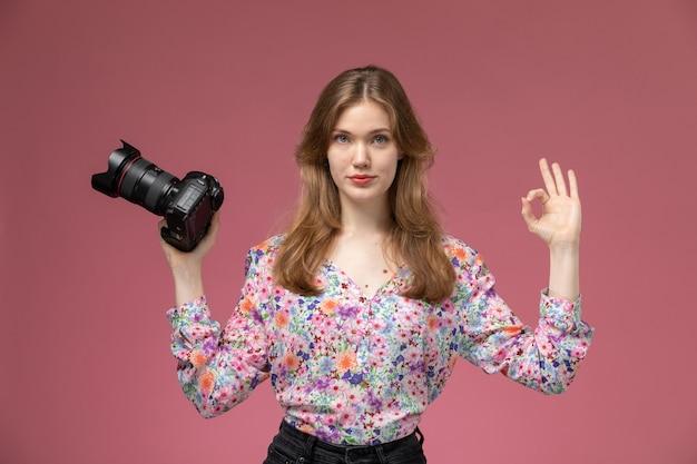Vue de face, jeune femme blonde montre que la photocaméra fonctionne bien