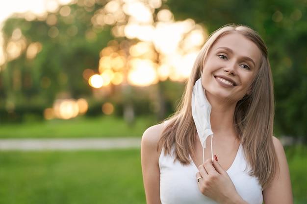 Vue de face de la jeune femme blonde séduisante décollant le masque de protection blanc, souriant avec les dents et regardant directement.