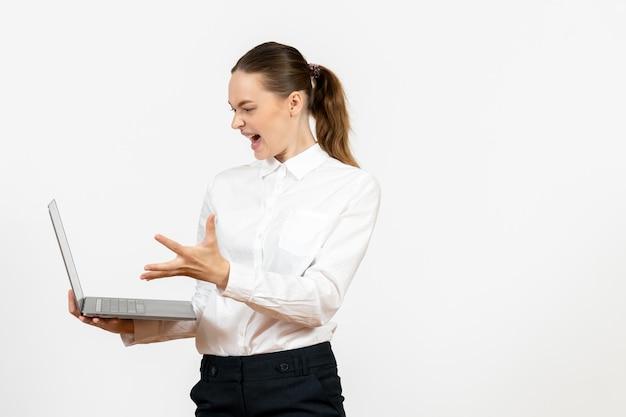 Vue de face jeune femme en blouse blanche à l'aide d'un ordinateur portable et criant sur fond blanc bureau d'emploi femme sentiment modèle émotion