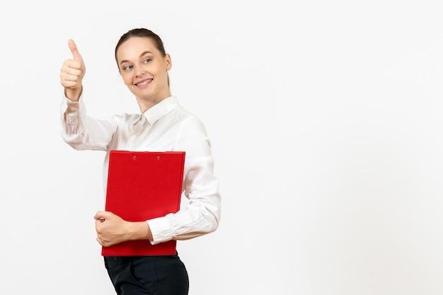 Vue de face jeune femme en blouse blanche avec dossier rouge dans ses mains sur fond blanc travail de bureau émotions féminines modèle de sentiment