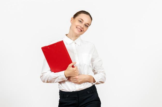 Vue de face jeune femme en blouse blanche avec dossier rouge dans ses mains sur fond blanc travail de bureau émotions féminines modèle de sentiments