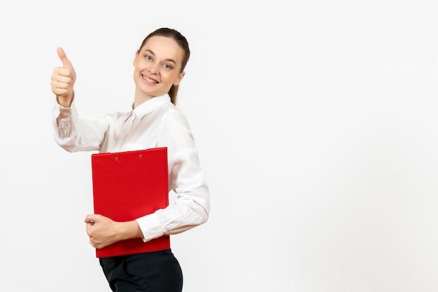 Vue de face jeune femme en blouse blanche avec dossier rouge dans ses mains souriant sur fond blanc travail de bureau émotion féminine modèle de sentiment
