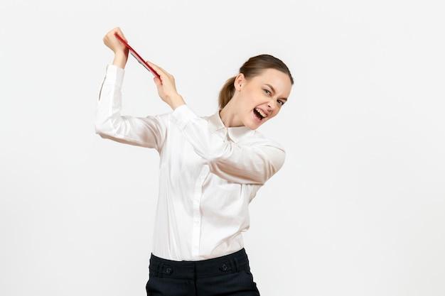 Vue de face jeune femme en blouse blanche avec dossier rouge se préparant à frapper avec elle sur fond blanc bureau émotions féminines sentiment travail modèle