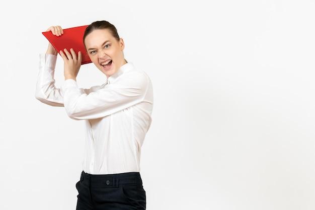 Vue de face jeune femme en blouse blanche avec dossier rouge se préparant à frapper avec elle sur fond blanc bureau sentiment féminin émotion travail modèle