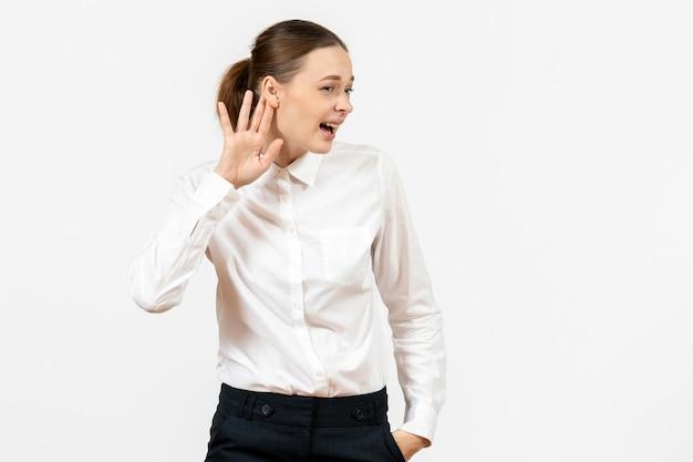 Vue de face jeune femme en blouse blanche essayant d'entendre sur fond blanc femme modèle bureau émotion sentiment d'emploi